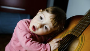 child rests ear on a guitar