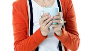 nervous woman holds mug