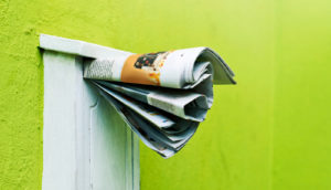 newspaper in mailbox on green wall