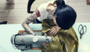 woman with tattooed arm uses a sewing machine