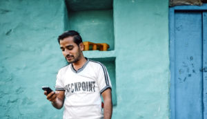 Indian man looks at phone