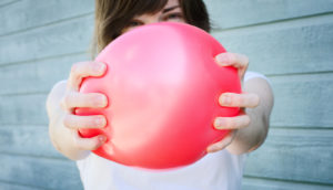 woman squeezes a balloon