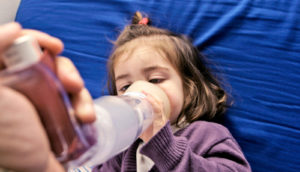 little girl uses inhaler