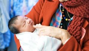older woman holds newborn