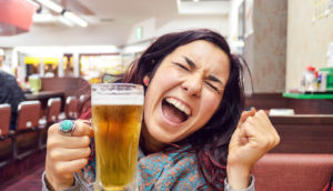 woman celebrates with a beer