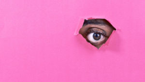 eye looks through pink paper