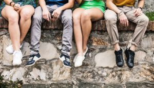 teens sit on stone wall