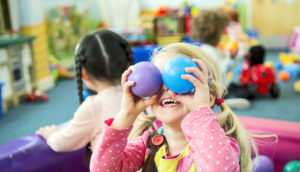 little girl puts colorful balls in front of her eyes