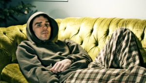 man in hoodie on couch