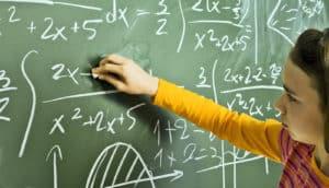 girl writes math on a chalkboard