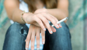 teenager holds a cigarette