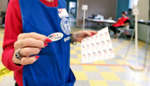 polling volunteer gives I voted sticker