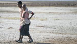 Hadza teens walk on the shore of Lake Eyasi