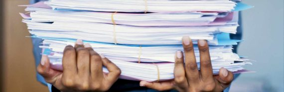 hands hold stack of paperwork