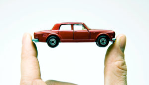 fingers hold red toy car