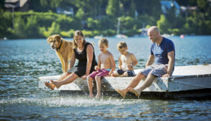 family splashes water from a dock on a lake