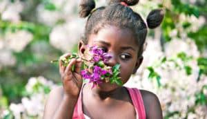 girl sniffs purple flowers