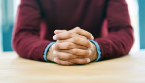 man's hands folded