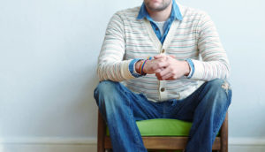 man sitting with hands folded