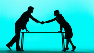 man, woman shake hands