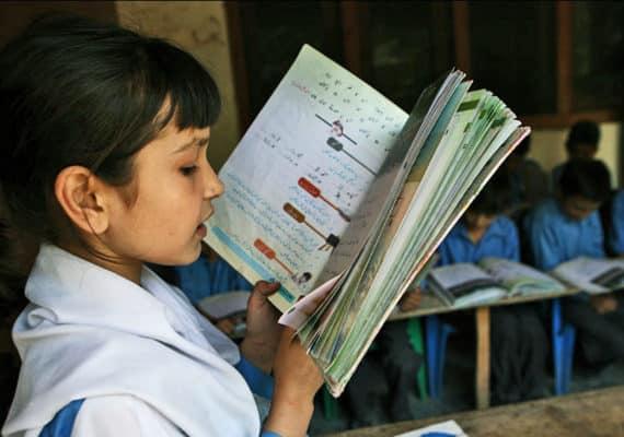 girl reads in Pakistani school