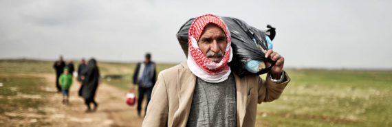 refugees walk land in syria
