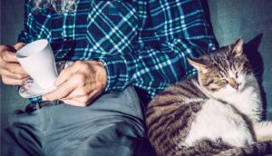 older man with tea and cat