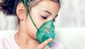 girl uses inhaler for asthma
