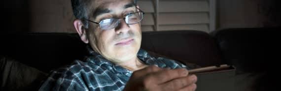 man uses tablet in dark