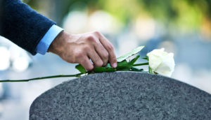 putting rose on grave stone
