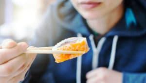 woman eats sushi