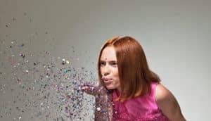 woman blows confetti