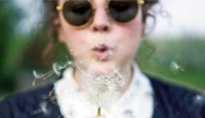 woman blows dandelion puff
