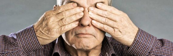 older man covers eyes with hands