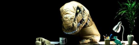 mean dinosaur boss looking sad at desk