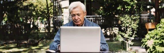 older man uses laptop outdoors