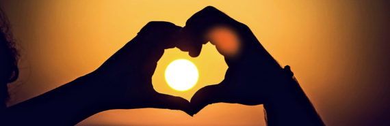 hands in the shape of a heart with sun in the background