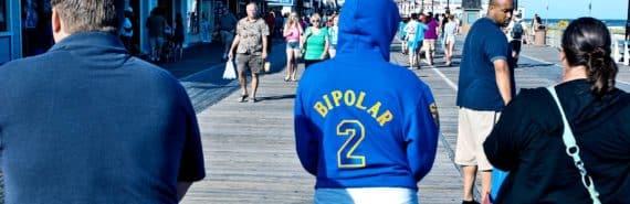 "woman wearing ""bipolar 2"" hoodie on boardwalk"