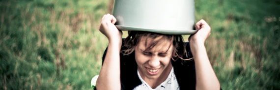 woman holds bucket on head