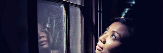 woman looks up and out window