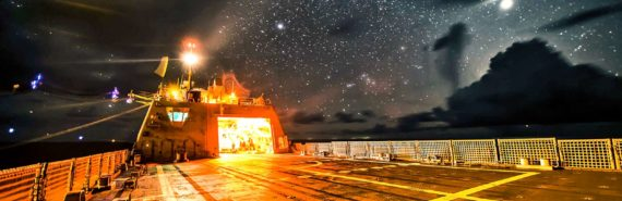 Naval ship under stars at night