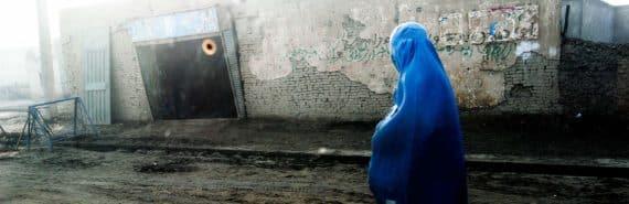 woman in blue walks in Afghanistan