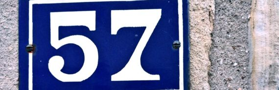 57 on blue plaque on concrete wall