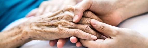 caregiver holding elderly hand