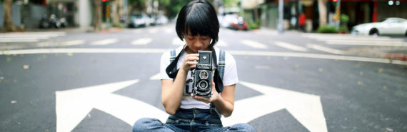 teen girl sits in street with camera