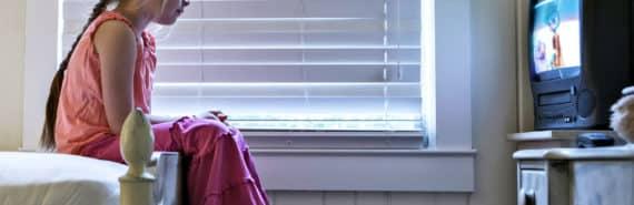 girl watches TV in bedroom