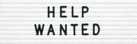 """black """"help wanted"""" on white sign"""