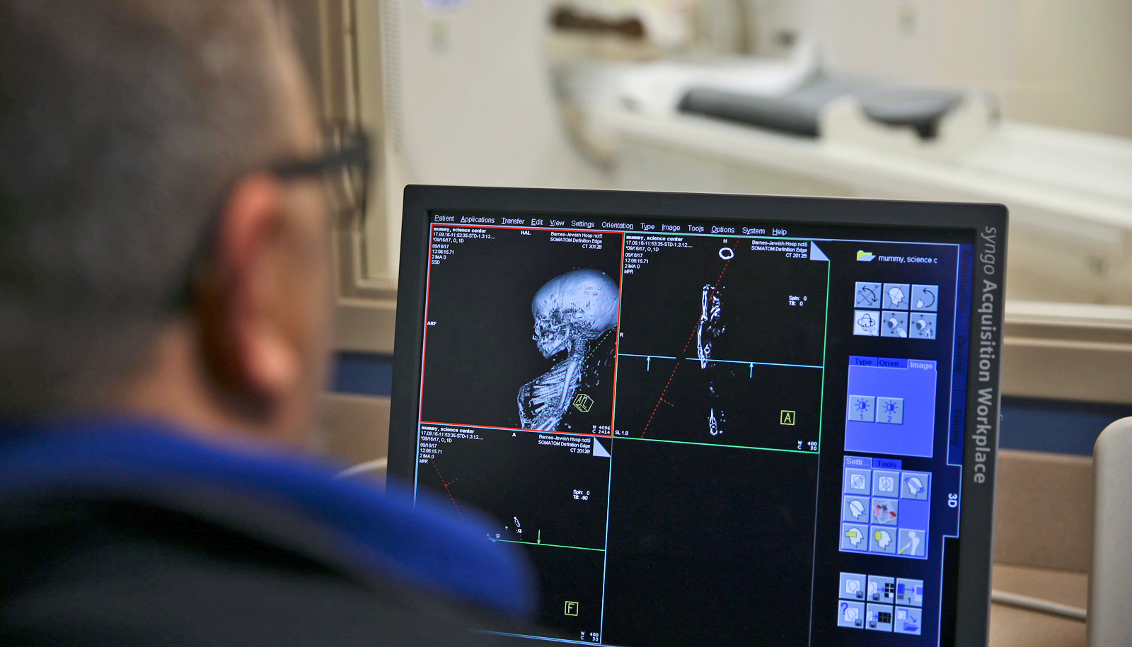 scientist looks at ct scan of baby mummy