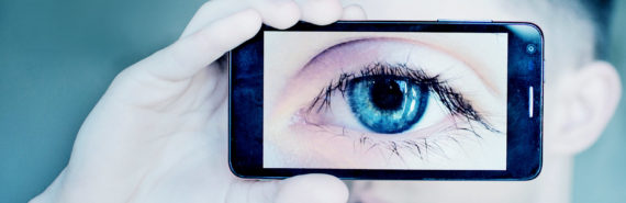 man holding smartphone to eyeball