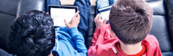 two boys using iPads